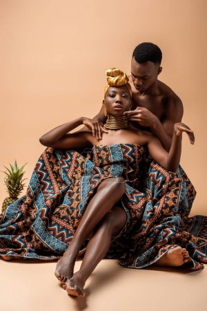 sexy naked tribal afro woman covered in blanket posing near man and pineapple on beige