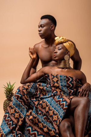 sexy naked tribal afro woman covered in blanket posing near man and pineapple isolated on beige