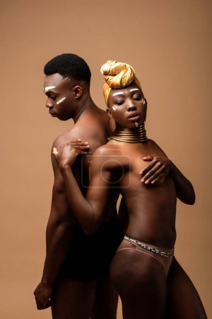 sexy naked tribal afro couple posing isolated on beige