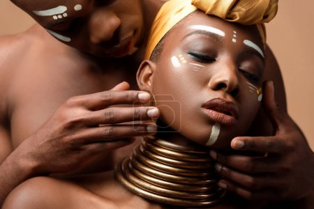 close up view of naked tribal afro couple posing isolated on beige