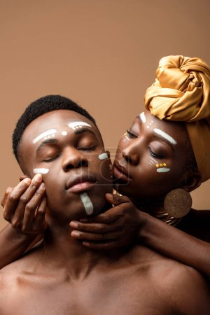 naked tribal afro couple with painted faces isolated on beige
