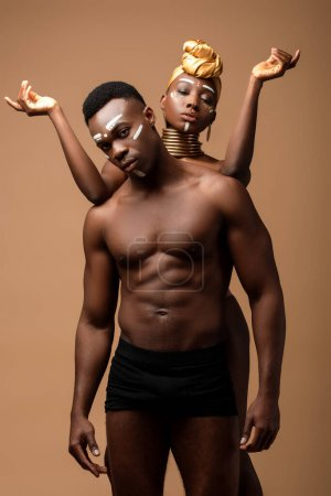 Photo for Naked tribal afro couple posing isolated on beige - Royalty Free Image