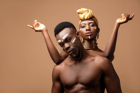 naked tribal afro couple posing isolated on beige