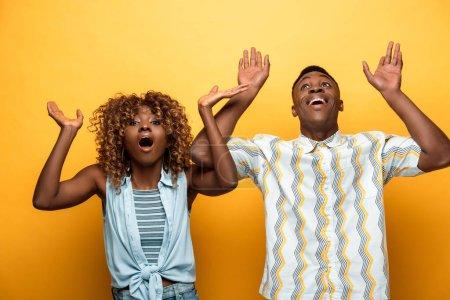 Photo pour Choqué couple afro-américain avec des bouches ouvertes gestuelle sur fond jaune coloré - image libre de droit