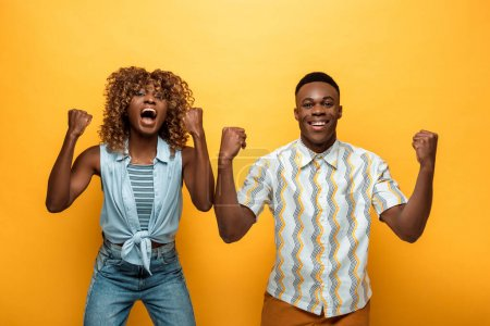 Photo for Happy african american couple showing yes gesture on yellow colorful background - Royalty Free Image