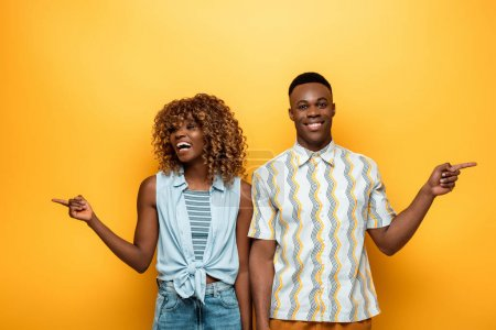 Photo for Happy african american couple pointing with fingers on yellow colorful background - Royalty Free Image