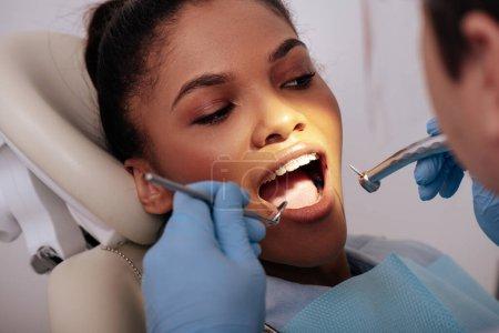 Photo pour Foyer sélectif du dentiste dans des gants en latex tenant des instruments dentaires près de femme afro-américaine attrayante dans des appareils - image libre de droit