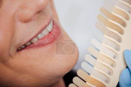 Photo pour Vue recadrée de l'homme souriant près de la palette des dents à la clinique - image libre de droit