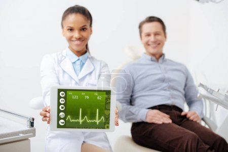 Photo for Selective focus of cheerful african american dentist holding digital tablet with heartbeat rate on screen near happy patient - Royalty Free Image