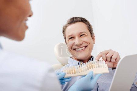 Photo pour Foyer sélectif de patient heureux pointant avec le doigt à la palette des dents près de dentiste afro-américain joyeux - image libre de droit
