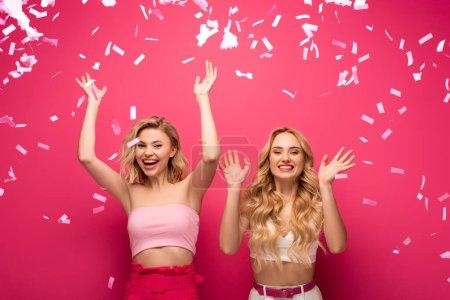 Photo pour Ami blond joyeux souriant à la caméra sous confettis tombant sur fond rose - image libre de droit