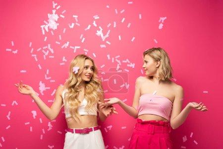 Photo pour Amis blonds confus se regardant sous les confettis tombants sur fond rose - image libre de droit