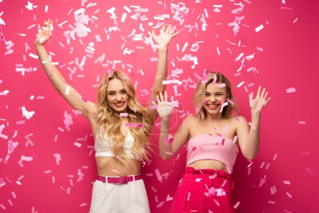 Photo for Happy blonde friends looking at camera under falling confetti on pink background - Royalty Free Image