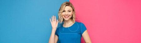 Photo pour Orientation panoramique de la fille blonde positive agitant la main à la caméra sur fond rose et bleu - image libre de droit