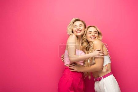 Photo pour Amis blonds souriants embrassant sur fond rose - image libre de droit