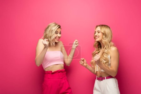 Photo for Cheerful blonde girls showing yeah gesture at each other on pink background - Royalty Free Image