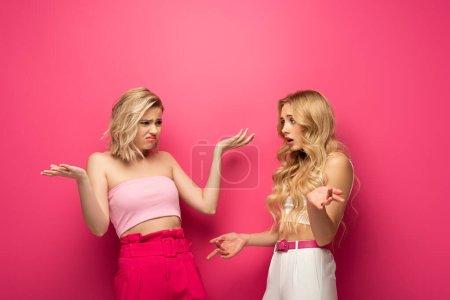 Photo pour Filles blondes offensées montrant un geste d'haussement d'épaules sur fond rose - image libre de droit