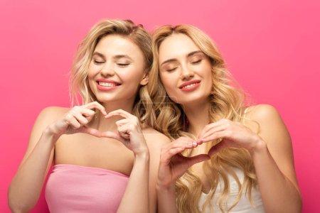 Photo pour Filles blondes souriantes avec les yeux fermés montrant signe du cœur sur fond rose - image libre de droit
