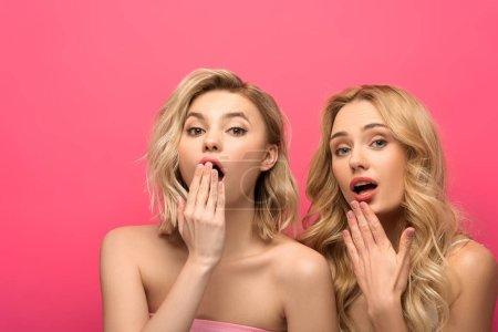 Photo pour Femmes blondes excitées regardant la caméra sur fond rose - image libre de droit