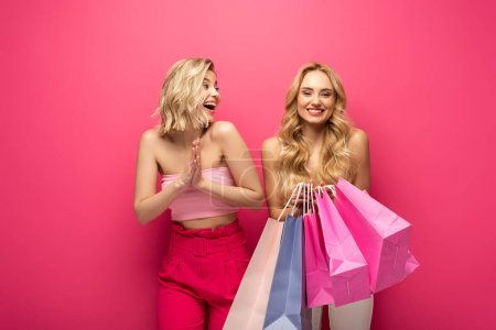 Photo for Cheerful blonde girl looking at friend holding shopping bags on pink background - Royalty Free Image