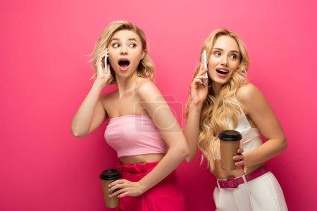 Photo pour Amis blonds excités tenant des tasses en papier tout en parlant sur les smartphones sur fond rose - image libre de droit