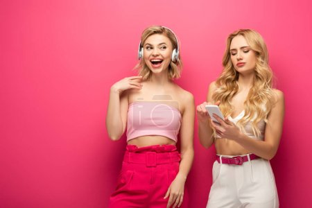 Photo pour Fille blonde joyeuse dans les écouteurs ami proche en utilisant un smartphone sur fond rose - image libre de droit