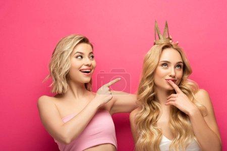 Photo pour Sourire femme blonde pointant sur cher ami en couronne sur fond rose - image libre de droit