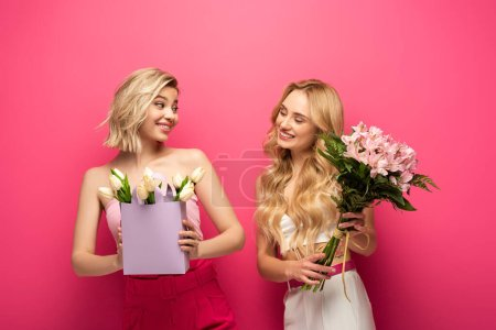 Photo pour Filles blondes avec des bouquets se souriant sur fond rose - image libre de droit