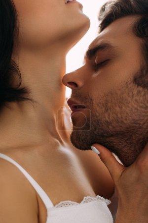 Photo pour Homme aux yeux fermés embrassant femme sur fond blanc - image libre de droit