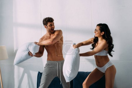 Photo pour Petit ami excité et petite amie se battant avec des oreillers sur le lit dans la chambre - image libre de droit
