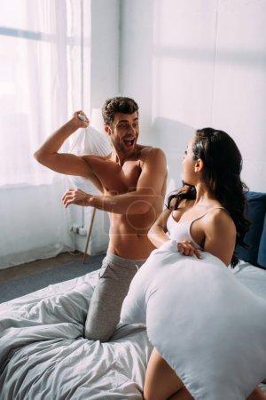 Photo pour Petit ami excité et petite amie se regardant et se battant avec des oreillers sur le lit dans la chambre - image libre de droit