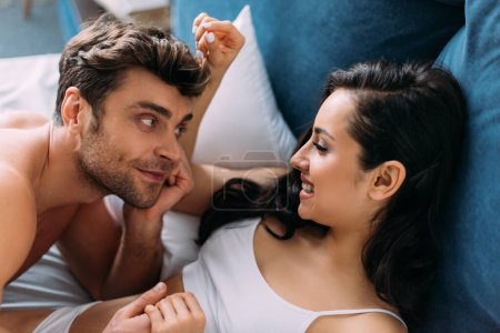 Photo for Woman and man smiling, holding hands and looking at each other on bed in bedroom - Royalty Free Image