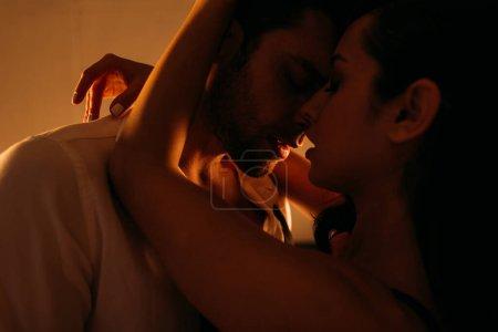 Photo pour Femme passionnée embrassant homme d'affaires avec les yeux fermés dans la chambre - image libre de droit