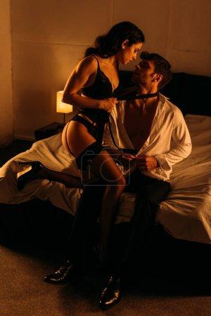 Photo pour Homme d'affaires déboutonner chemise près de femme sexy tenant cravate sur le cou masculin sur le lit dans la chambre - image libre de droit