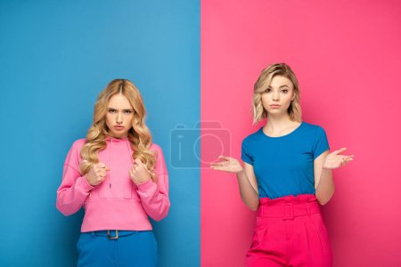 Photo for Angry woman with fists looking at camera near blonde sister showing confused sign on pink and blue background - Royalty Free Image