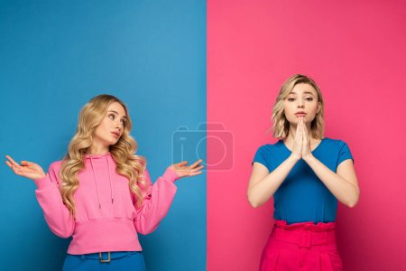 Photo pour Attractive blonde girl with shrug gesture looking at sister with prayer hands on pink and blue background - image libre de droit