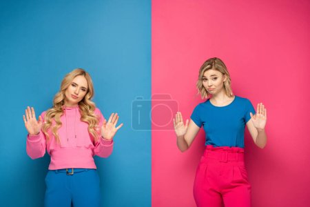 Photo pour Soeurs blondes confuses montrant geste d'arrêt à la caméra sur fond rose et bleu - image libre de droit