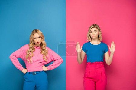 Photo pour Sœurs blondes avec les mains sur les hanches montrant geste d'arrêt sur fond rose et bleu - image libre de droit