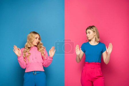 Photo for Confused blonde girls showing stop gesture on pink and blue background - Royalty Free Image