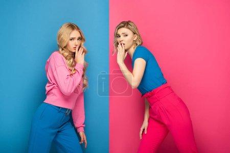 Photo pour Vue latérale de filles blondes montrant signe calme sur fond rose et bleu - image libre de droit