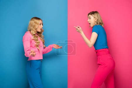 Photo for Side view of excited blonde sisters showing shrug gesture and pointing with finger on pink and blue background - Royalty Free Image