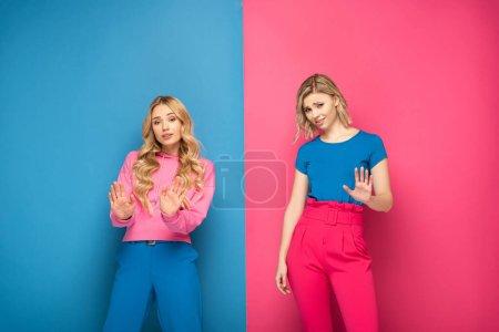 Photo pour Belles femmes blondes montrant geste d'arrêt sur fond rose et bleu - image libre de droit