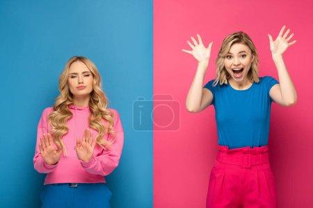 Photo pour Femme blonde montrant stop signe près soeur excitée sur fond rose et bleu - image libre de droit