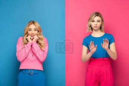 Photo pour Femme souriante regardant la caméra près de soeur blonde montrant stop signe sur fond bleu et rose - image libre de droit