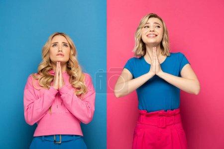 Photo pour Sœurs blondes avec des mains de prière regardant loin sur fond rose et bleu - image libre de droit