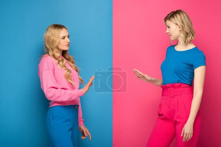 Photo for Offended blonde sisters showing stop gesture on pink and blue background - Royalty Free Image