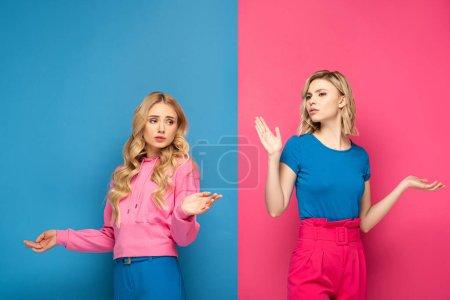 Photo pour Filles blondes confuses montrant geste haussant les épaules sur fond rose et bleu - image libre de droit
