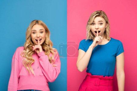Photo pour Sœurs blondes excitées montrant signe de silence à la caméra sur fond rose et bleu - image libre de droit