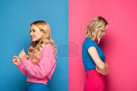 Photo pour Vue latérale de triste fille blonde près de soeur montrant un geste oui sur fond rose et bleu - image libre de droit