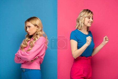 Photo pour Triste blonde fille regarder loin près heureux soeur montrant ouais geste sur rose et bleu fond - image libre de droit